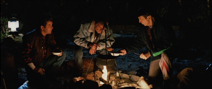 Enjoying a campfire meal together - Kirk, Spock, and McCoy