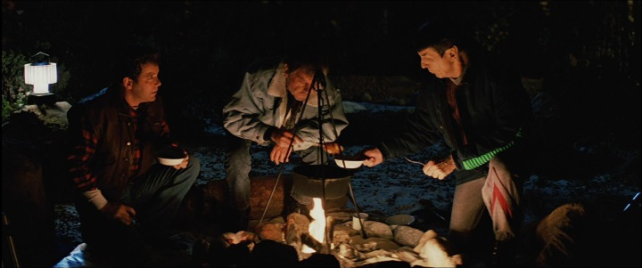 Enjoying a campfire meal together - Kirk, Spock, and McCoy