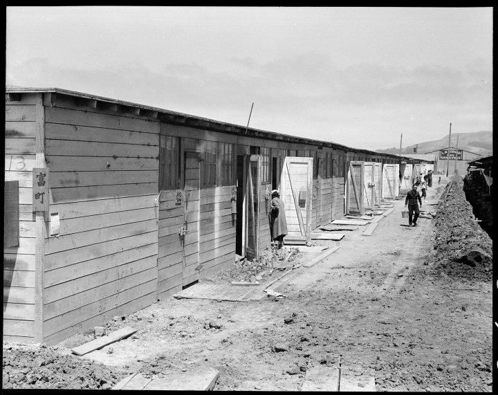 San Bruno, California. This scene shows one type of barracks for family use. These were formerly the stalls for race horses. Each family is assigned to two small rooms, the inner one, of which, has no outside door nor window. The center has been in operation about six weeks and 8,000 persons of Japanese ancestry are now assembled here. (another Dorothea Lange image from the AnchorEditions collection)
