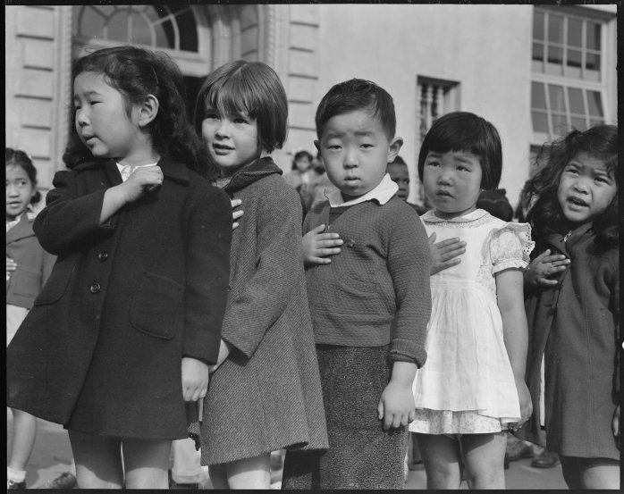 San Francisco, California. Many children of Japanese ancestry attended Raphael Weill public School, Geary and Buchanan Streets, prior to evacuation. This scene shows first- graders during flag pledge ceremony. Evacuees of Japanese ancestry will be housed in War Relocation Authority centers for the duration. Provision will be effected for the continuance of education. (from the Dorothea Lange collection as shown on the AnchorEdition website)