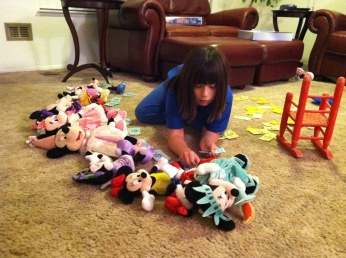 Emma playing Monopoly with her Minnie Mouse dolls